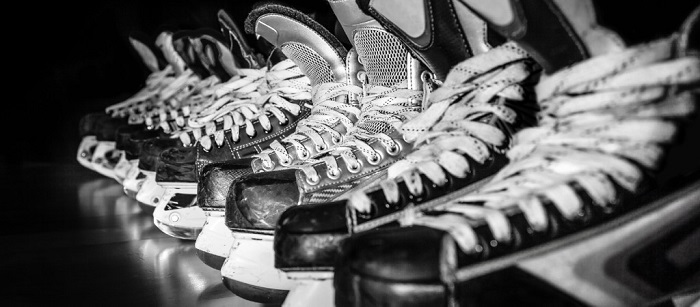 Black and white hockey skates in a row.