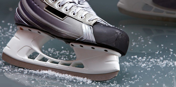 Close-up of skates on player feet during ice hockey.