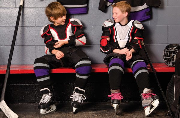 Young boys sitting in hockey jerseys.